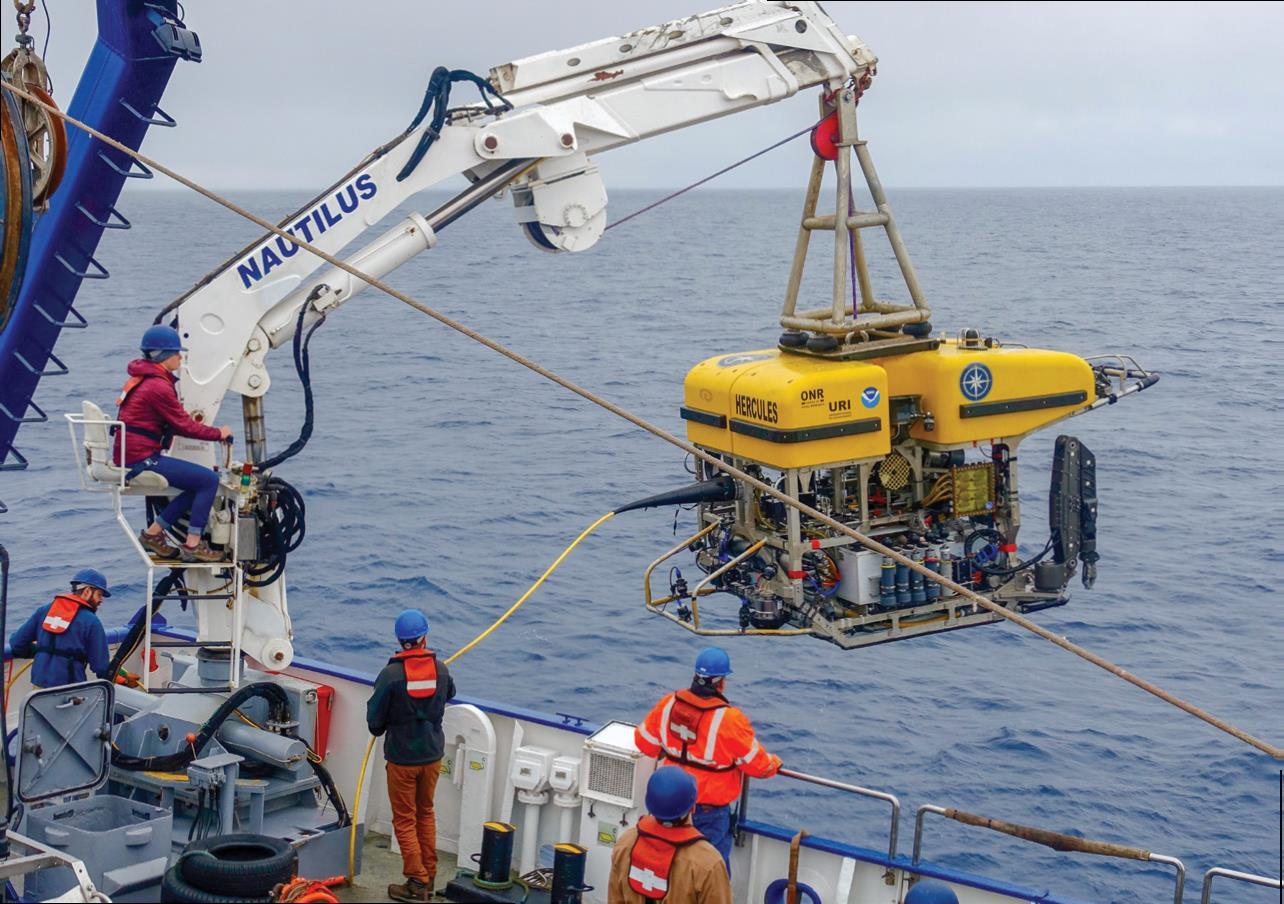 Crew aboard the E/V Nautilus carefully maneuvering the immersion of Hercules, a remotely operated vehicle, during the 2018 Expedition to SK-B Seamount. Photo credit: Oceans Network Canada