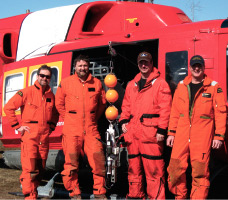 The survey crew in March 2010: Rémi Desmarais, Electronics Technician, and Peter Galbraith, Researcher, Oceanography and Physical Modeling, both of Fisheries and Oceans Canada; Robert Audette, Aircraft Maintenance Engineer, and Daniel Dubé, Helicopter Pilot, both of Transport Canada. The probe used is in the centre of the group.